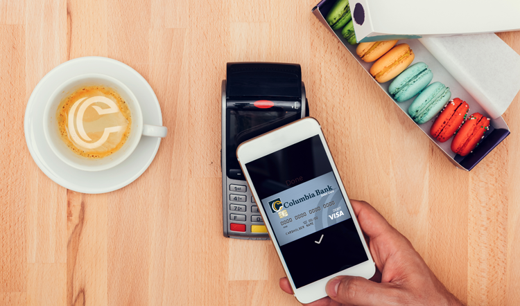 A person paying for coffee and macaroons with mobile payment on their phone.